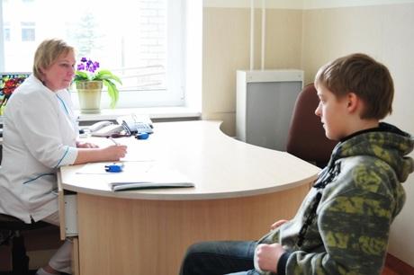 Vaikas su slaugytoja priėmimo skyriuje Skuode