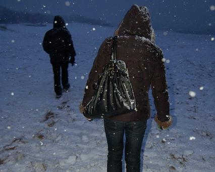 Du žmonės žiemą eina keliu