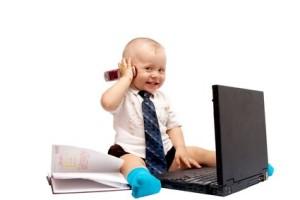 Vaikas prie kompiuterio laiko telefoną