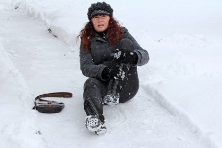 Moteris ant sniego susiėmusi už kojos