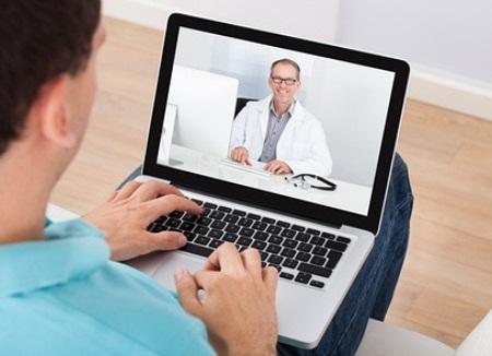 Vyras žiūri į kompiuterio ekrane matomą gydytojo veidą