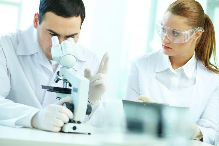 Laborantas žiūri pro mikroskopą