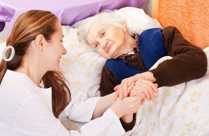 Medikė laiko gulinčios senutės ranką