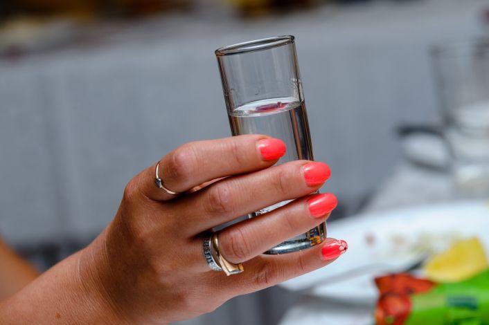 Rankoje laiko stikliuką su degtine