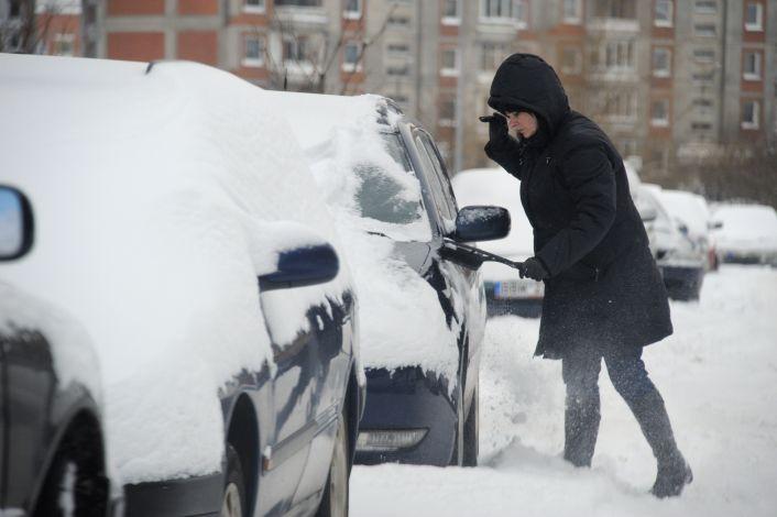 Moteris valo sniegą nuo automobilio