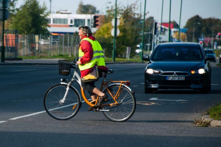 Moteris važiuoja dviračiu per gatvę