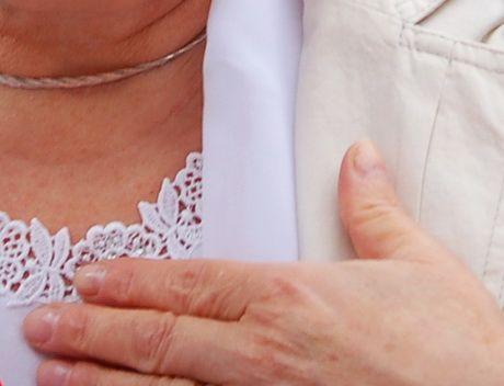 Moteris ant krūtinės pridėjusi ranką