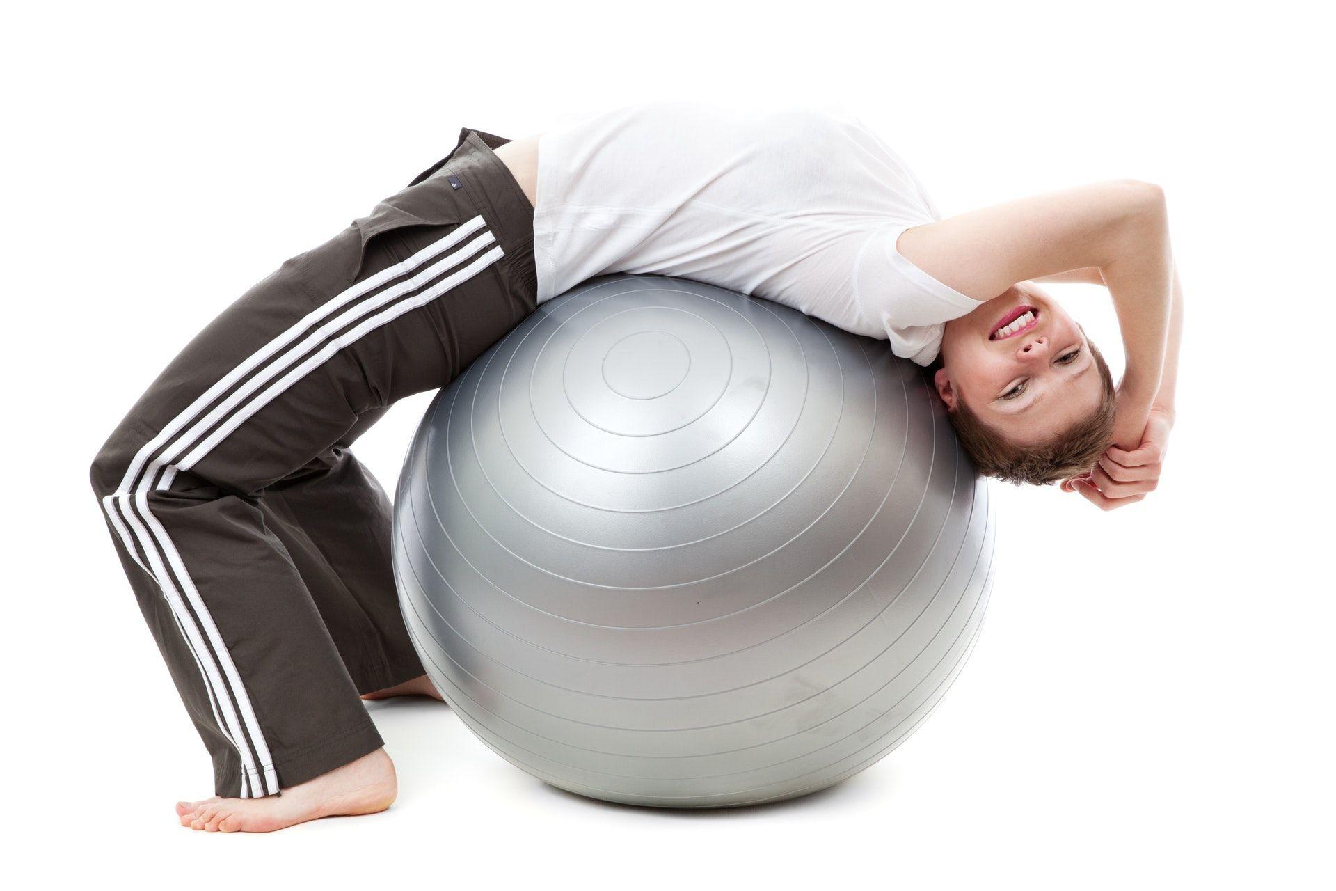 Vaikas, nugara atsigulęs ant gimnastikos kamuolio