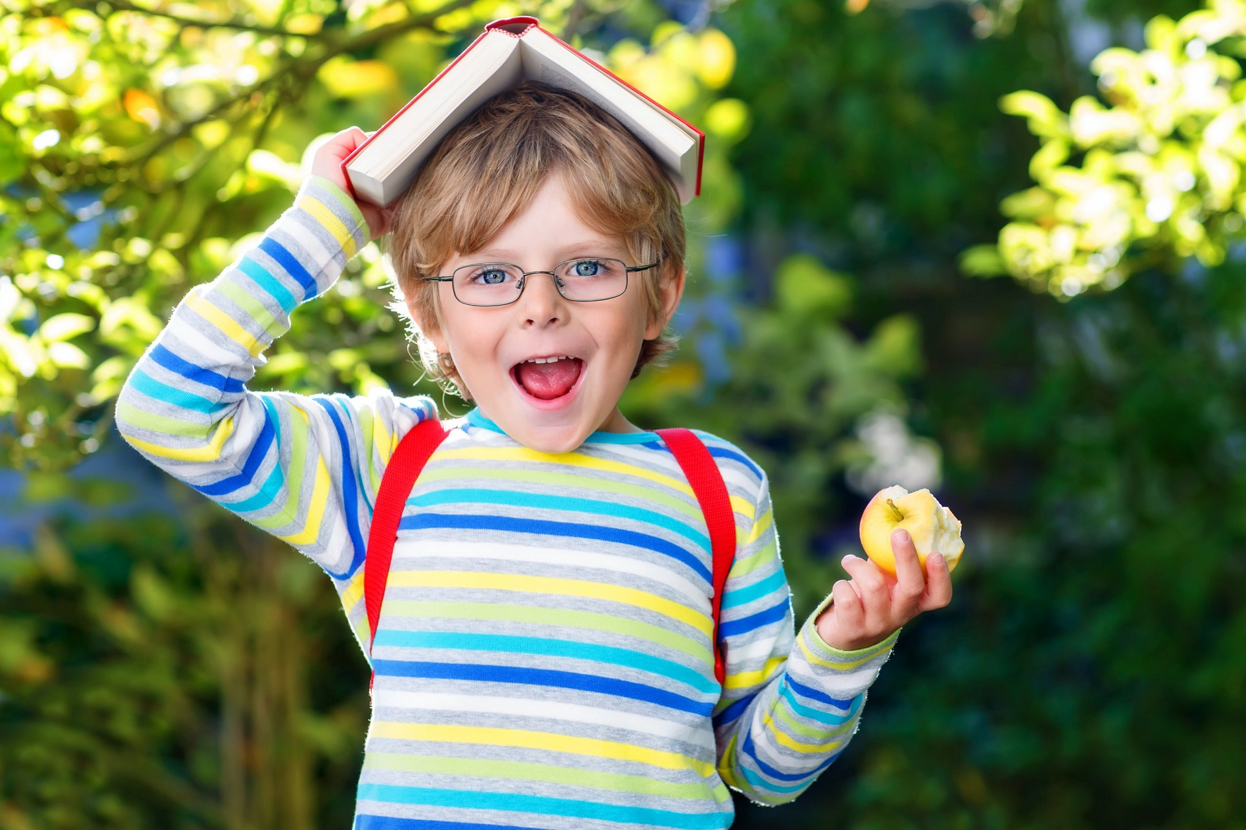 Vaikas su knyga ir obuoliu