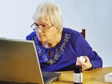 Moteris su akiniais žiūri į kompiuterio ekraną