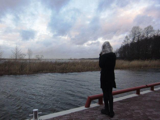 Mergina žiūri į vandenį