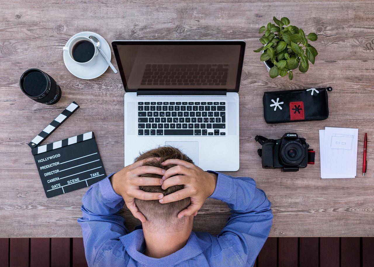 Žmogus prie kompiuterio susiėmęs už galvos