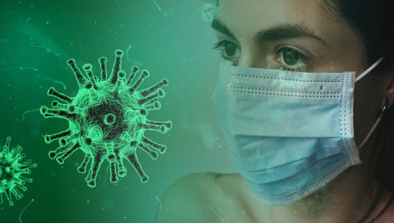 Moteris su kauke priešais koronaviruso vaizdą