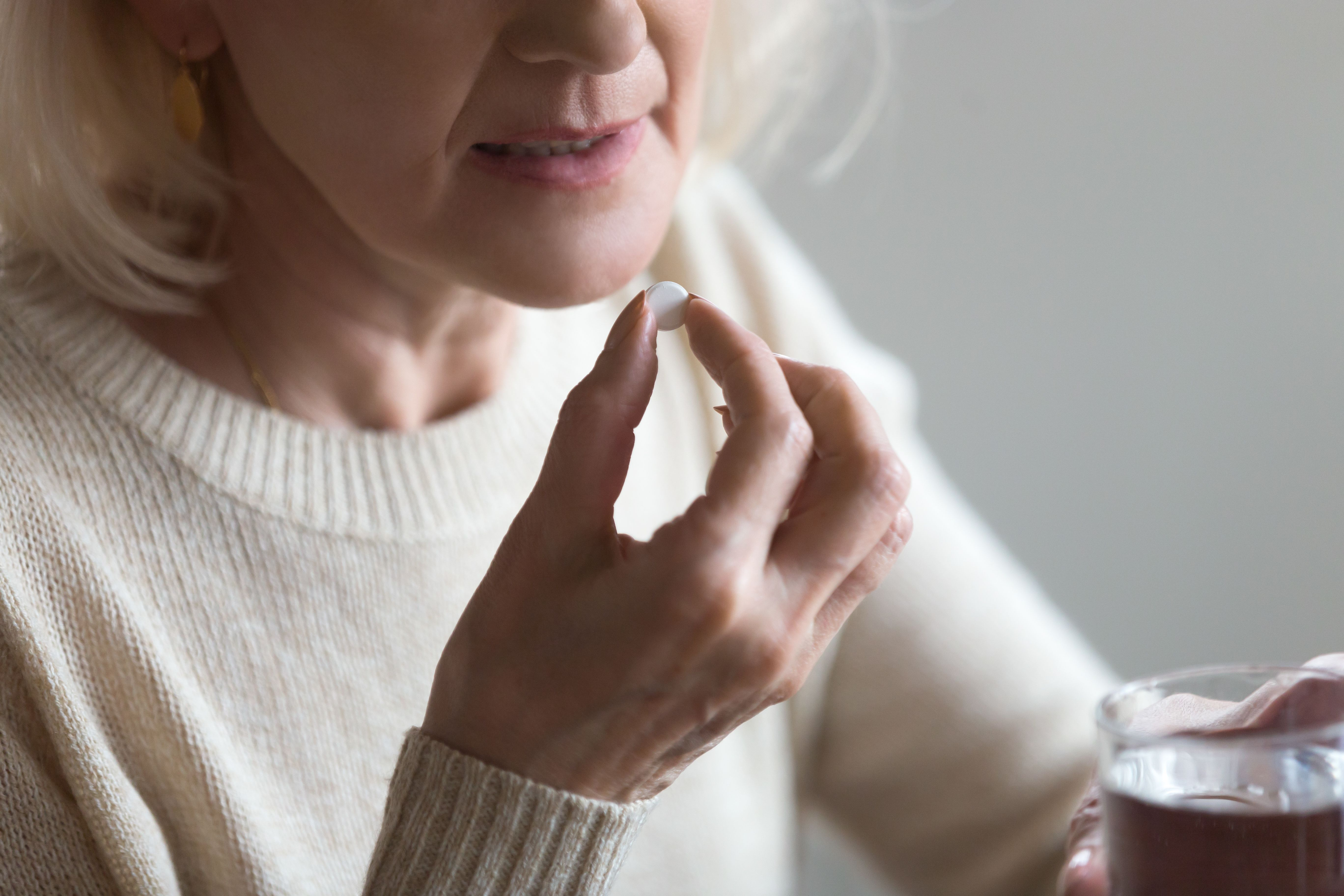 Moteris į burną deda tabletę