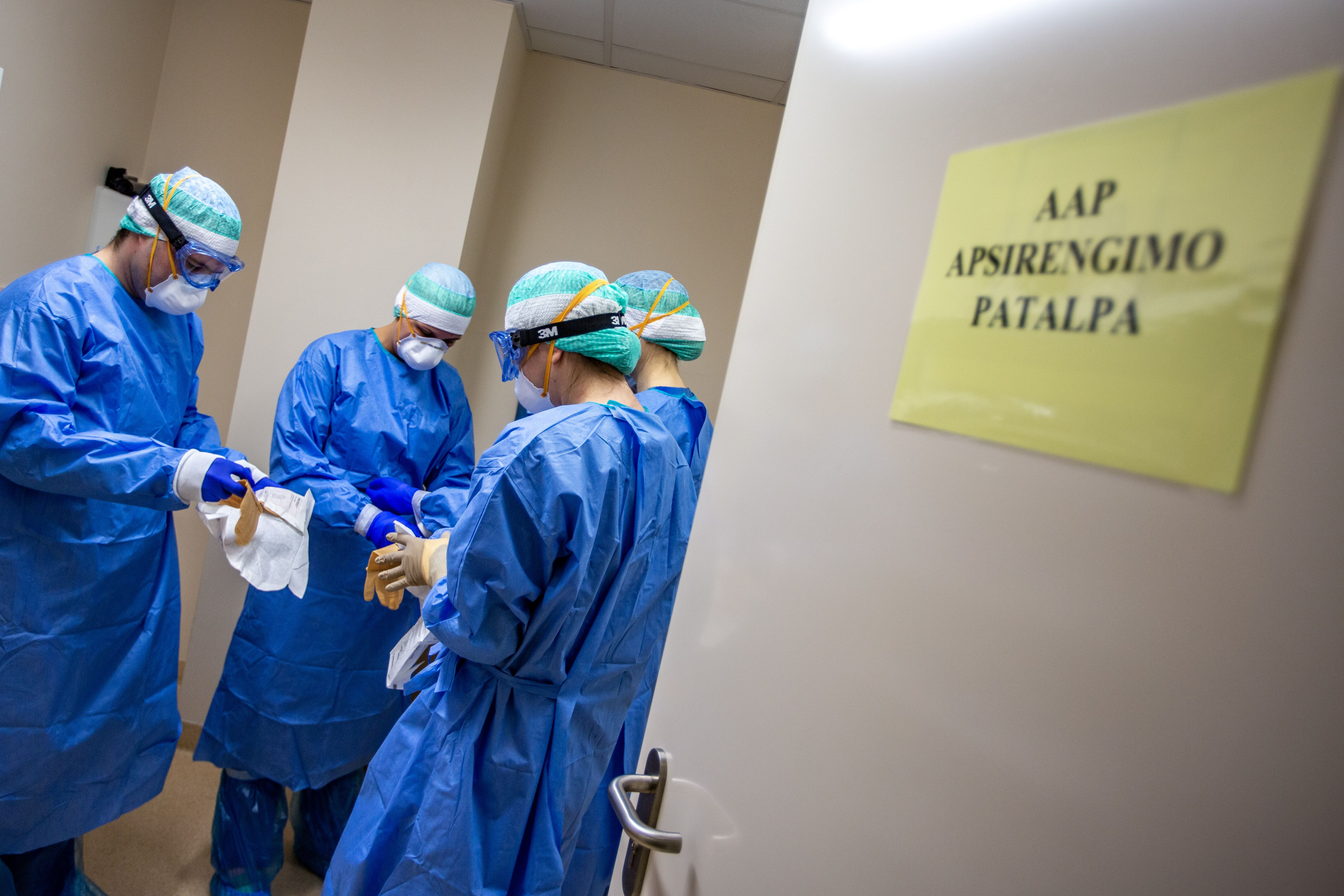 Keturi gydytojai su kaukėmis maunasi pirštines