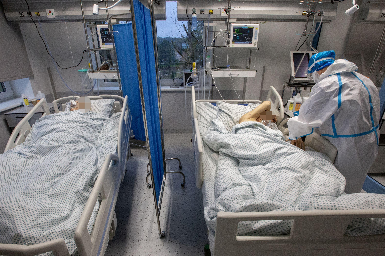 Dvi reanimacijos lovos su pacientais ir medikas šalia