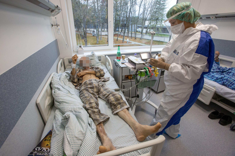 Ligonis lovoje ir šalia medikė su kauke