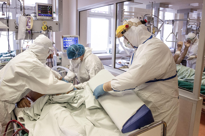 Trys medikai su kaukėmis slaugo ligonį