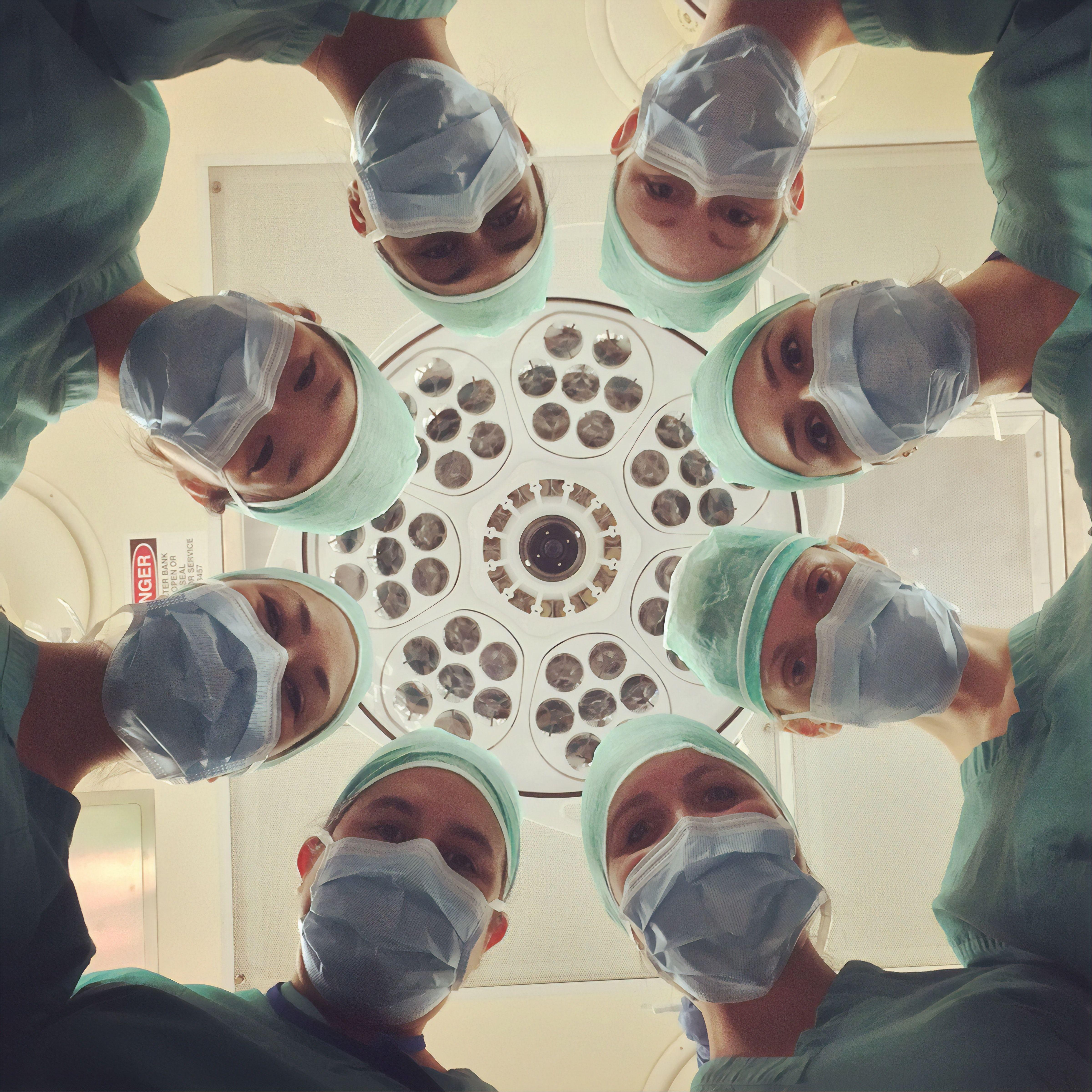 Chirurgai operacinėje palinkę virš stalo
