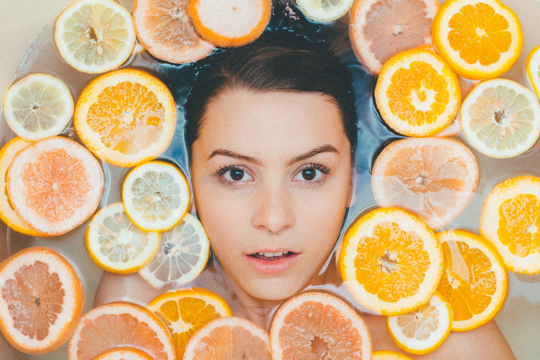 Moters veidas vandens vonelėje su apelsinų griežinėliais
