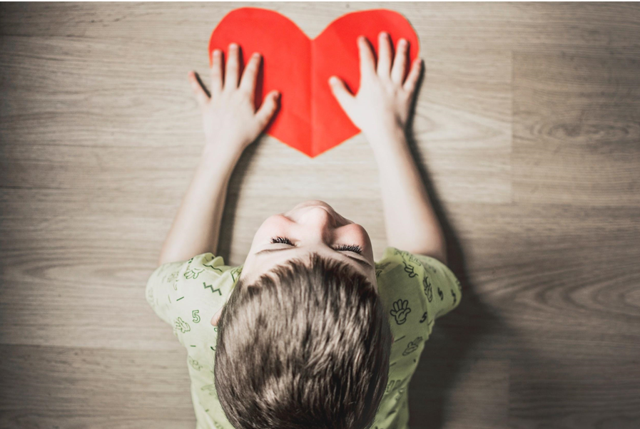 Vaiko rankos ant širdies formos piešinio