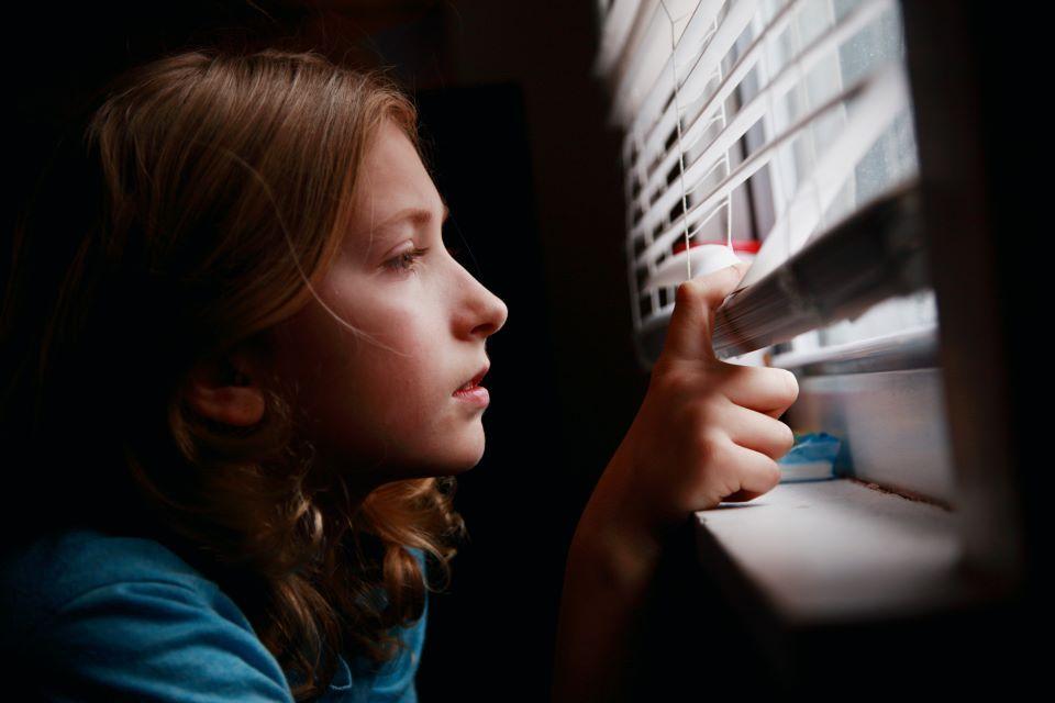 Mergaitė žiūri pro langą