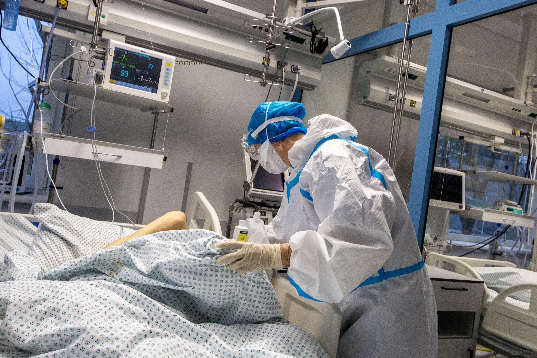 Medikas su kauke pasilenkęs prie ligonio