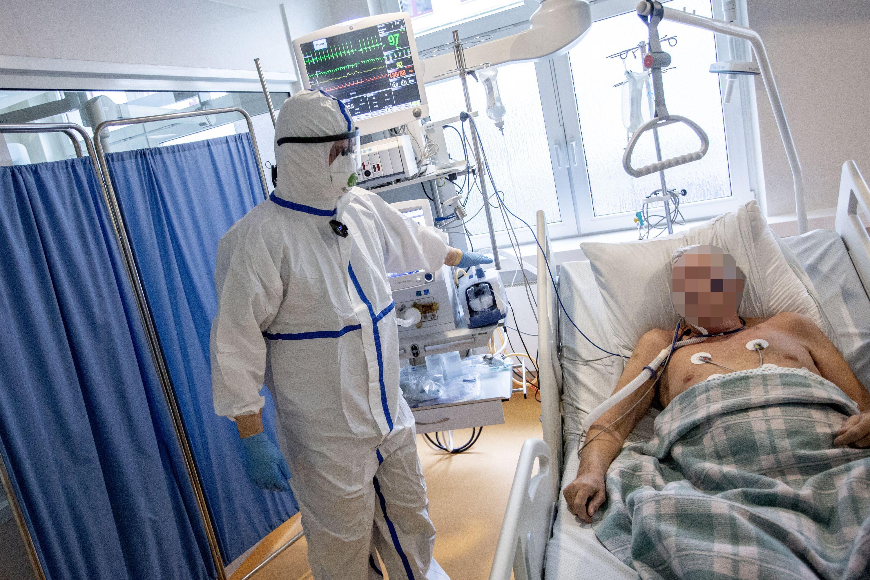 Medikas su apsaugine apranga prie ligonio lovos