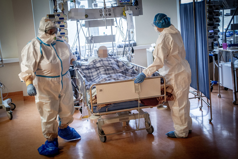 Du medikai su apsaugine apranga šalia ligonio lovos