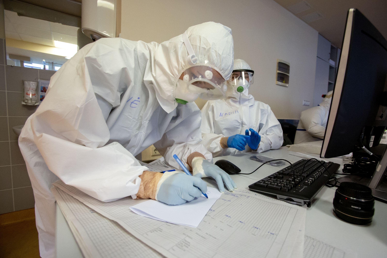 Medikai su apsaugine apranga rašo dokumentą