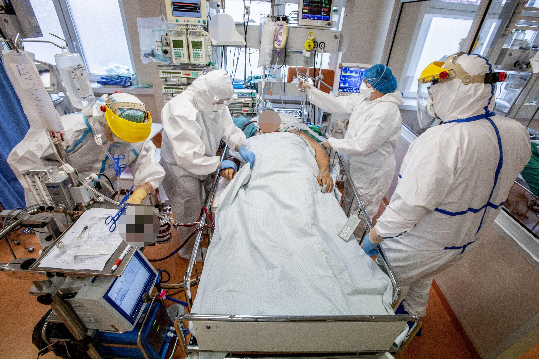 Keturi medikai prie ligonio lovos
