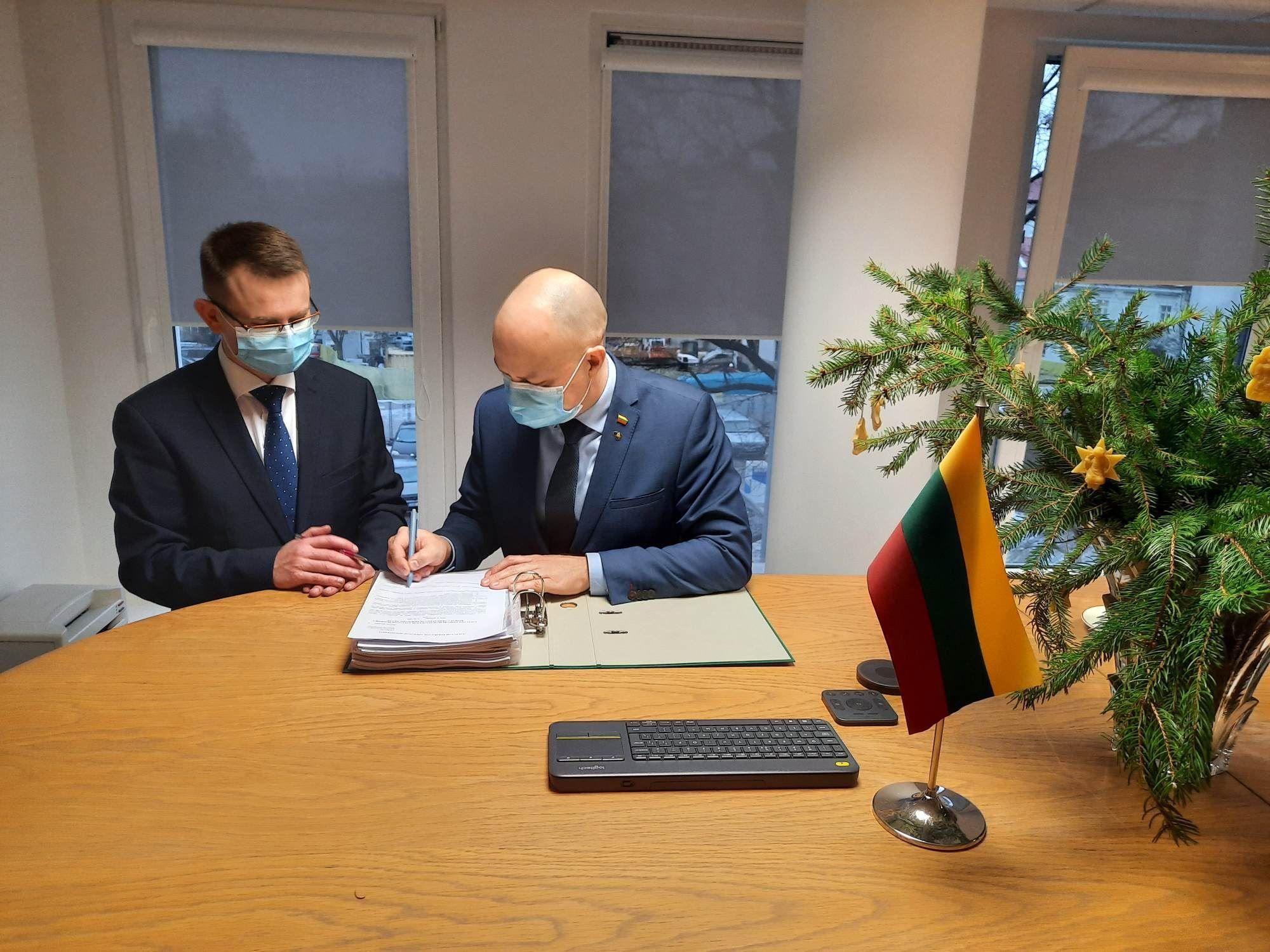 Arūnas Dulkys ir Aurelijus Veryga pasirašo dokumentą
