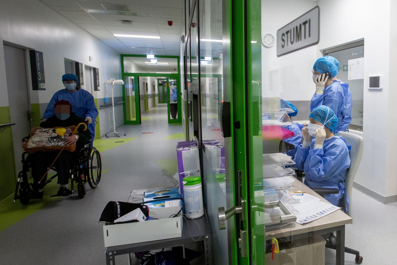 LIgoninės koridoriuje vežamas ligonis, stovi slaugytojos
