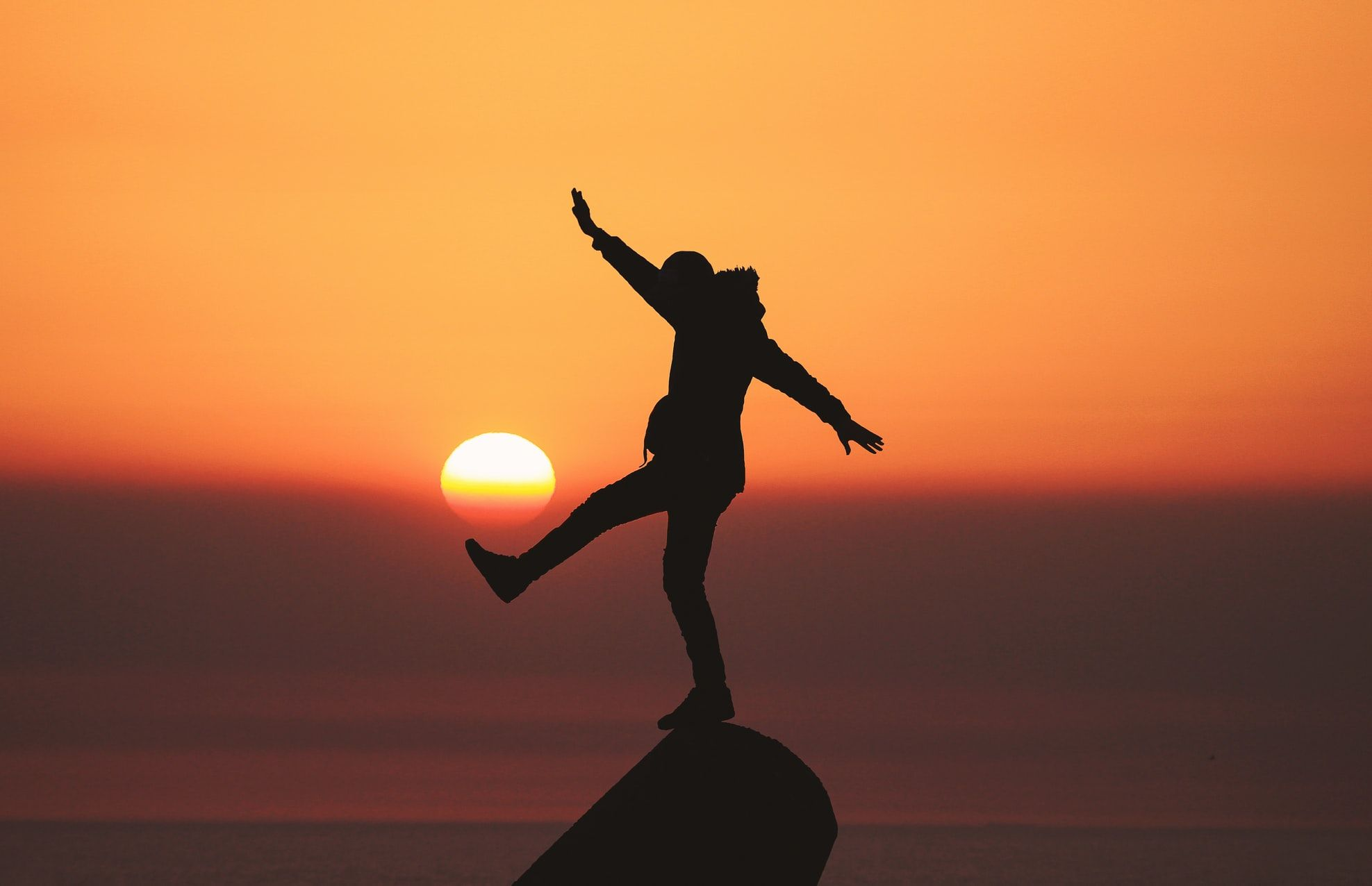 Žmogus ant uolos stovi ant vienos kojos