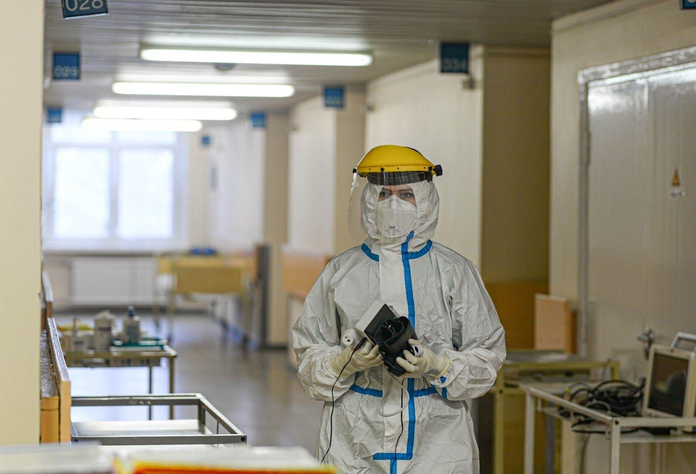 Medikas su apsaugine apranga ligoninės koridoriuje