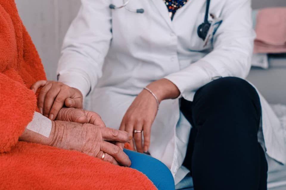 Gydytoja padėjusi ranką ant pacientės rankų