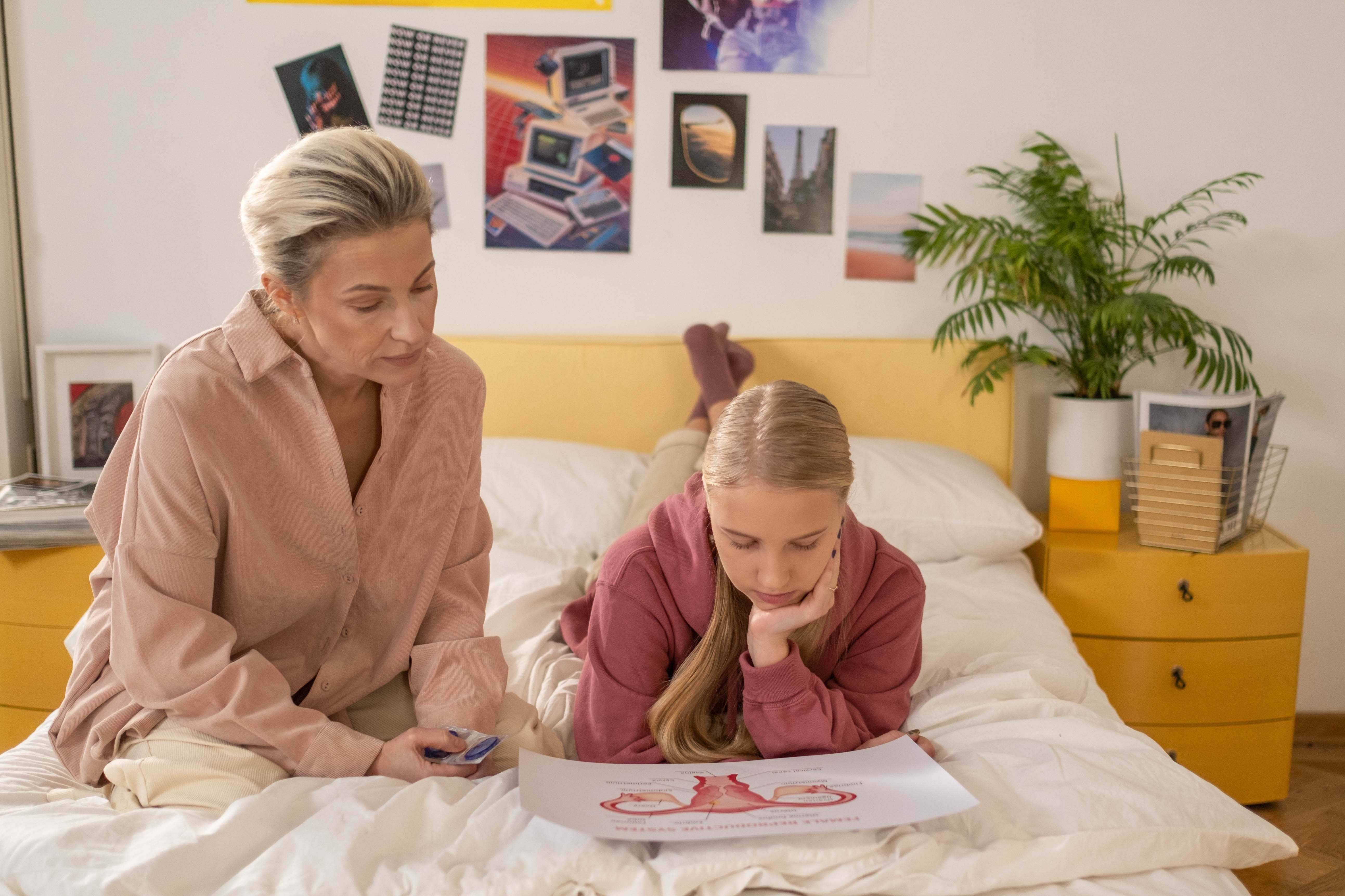 Mama ir paauglė dukra guli ant lovos ir žiūri į paveksliuką