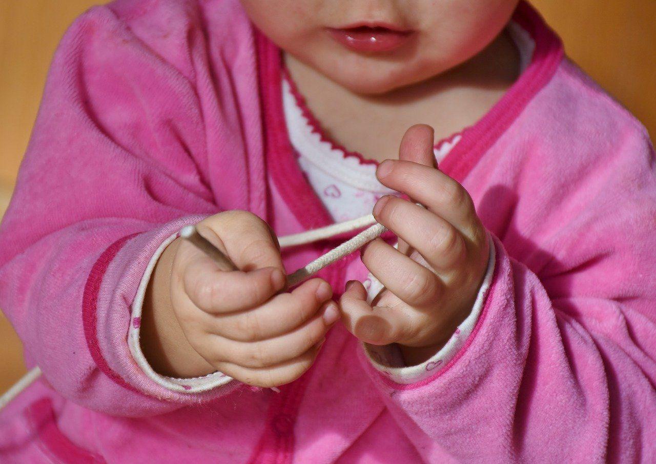 Vaikas lavina pirštus su virvute