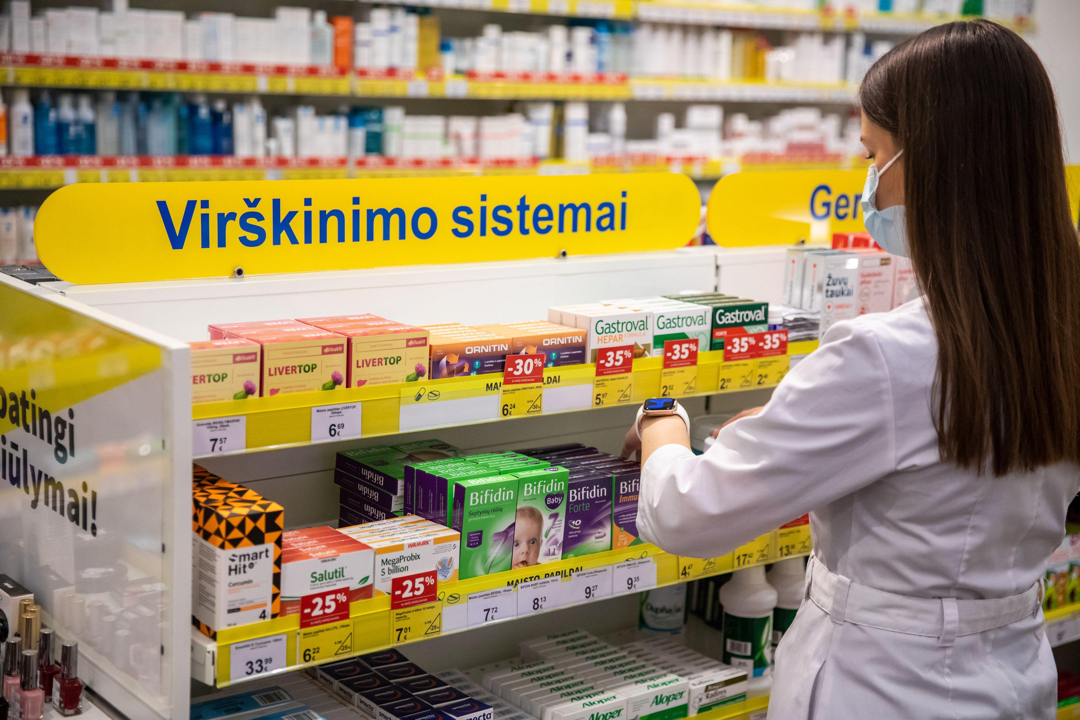 Vaistininkė prie vaistų lentynos