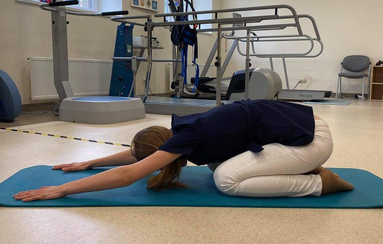 Mergina atlieka nugaros raumenų atpalaidavimo pratimą