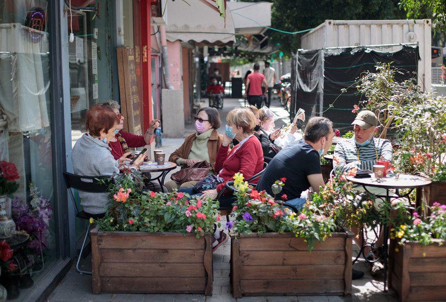 Žmonės su kaukėmis sėdi lauko kavinėje