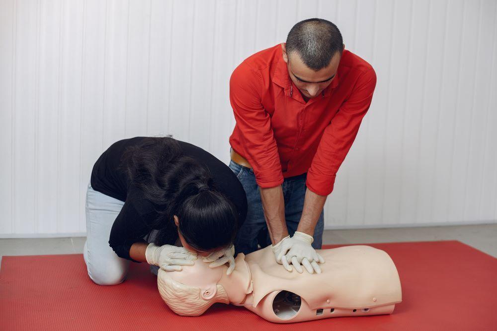 Du žmonės demonstruoja dirbtinį kvėpavimą