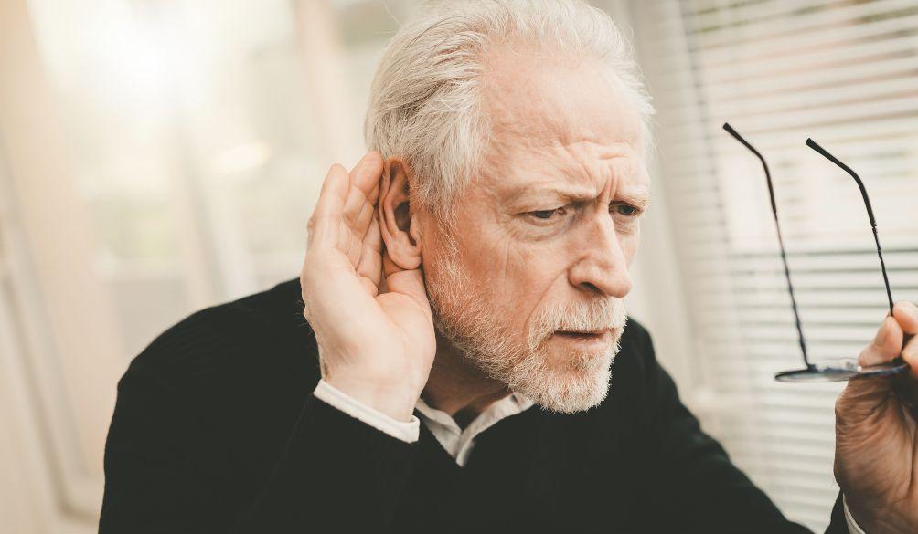 Neprigirdintis senukas ranką laiko ant ausies