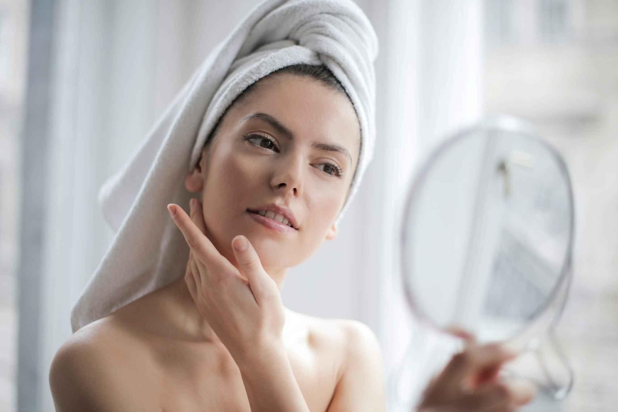 Mergina žiūri į veidrodį