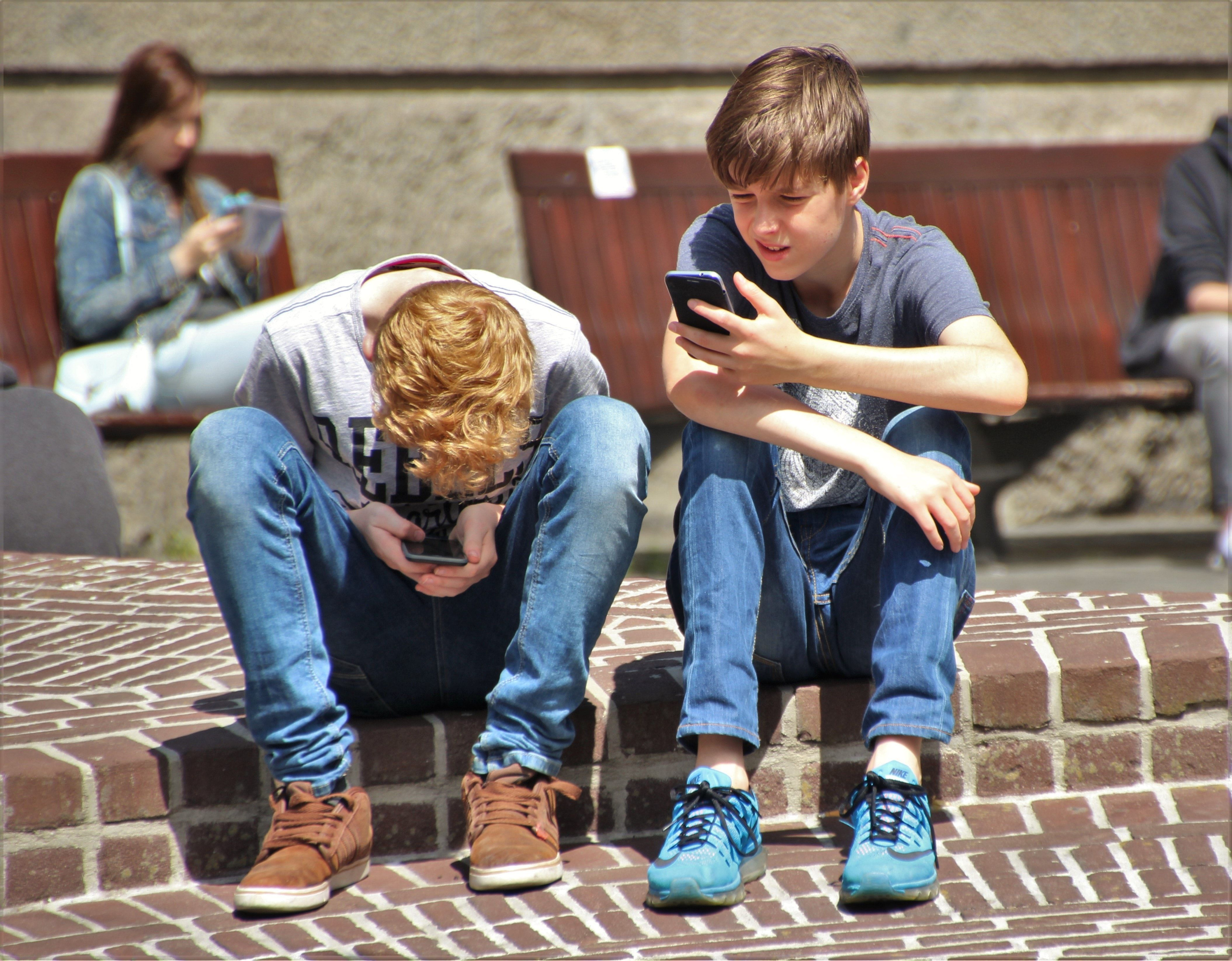 Du paaugliai žiūri į telefonus